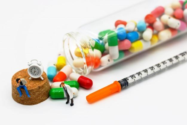 Pessoas em miniatura, pacientes sentados com drogas e relógio