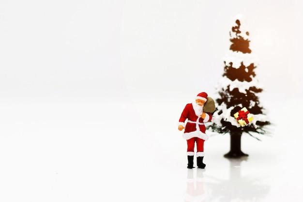 Pessoas em miniatura: papai noel com árvore de natal.