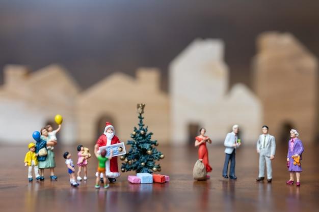 Pessoas em miniatura: papai noel e família feliz