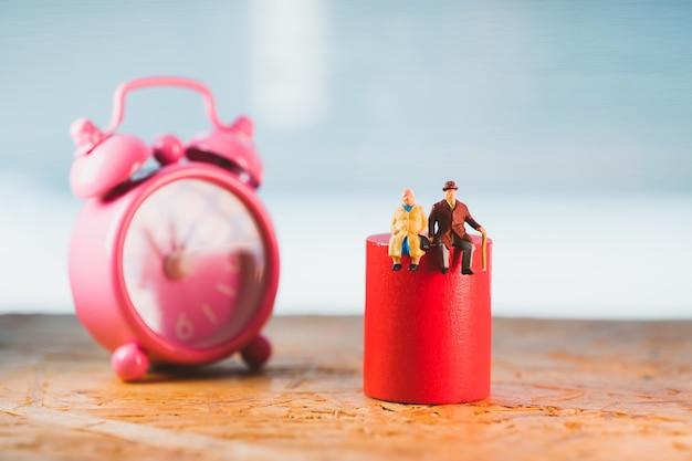 Pessoas em miniatura, pessoas idosas sentadas na madeira vermelha com o fundo do relógio usando como aposentadoria de emprego e conceito de seguro de vida