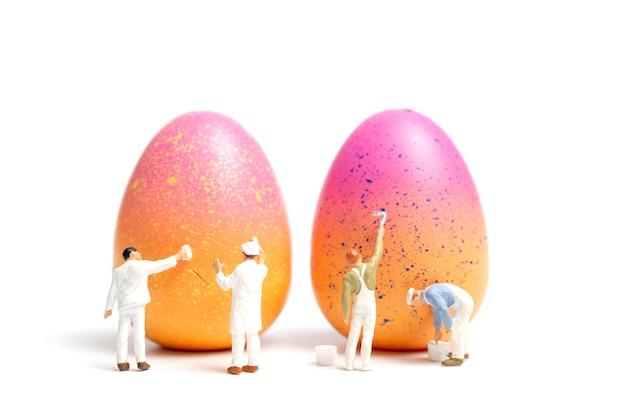 Pessoas em miniatura pintando ovos de páscoa