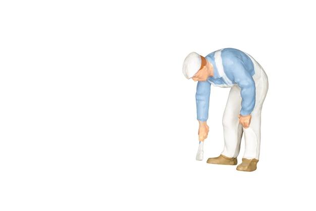 Pessoas em miniatura: pintor segurando um pincel isolado no branco e traçado de recorte