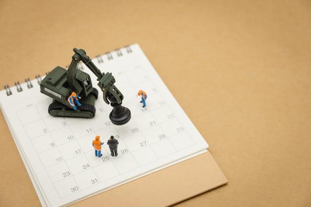Pessoas em miniatura reparação de trabalhador de construção com calendário branco
