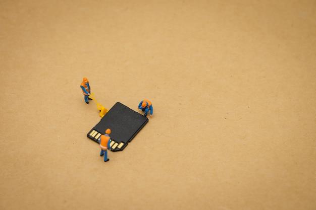 Pessoas em miniatura reparação de trabalhador de construção com cartão de armazenamento ou cartão de memória