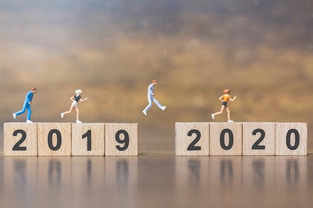 Pessoas em miniatura salta do número 2019 para 2020