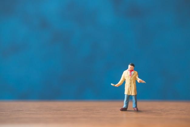Pessoas em miniatura, segurando o pincel na frente de um fundo de parede azul