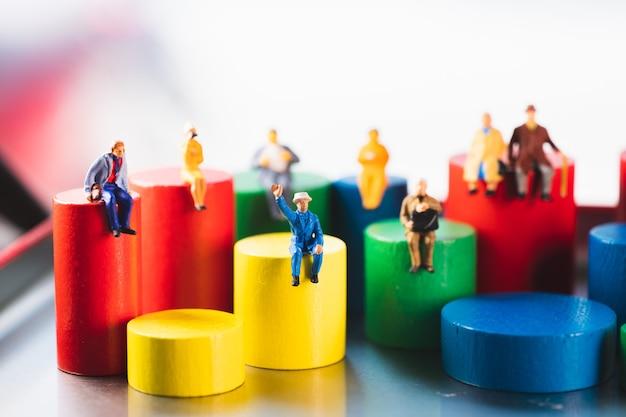 Pessoas em miniatura sentadas em um bloco de madeira colorido usando como conceito familiar e social