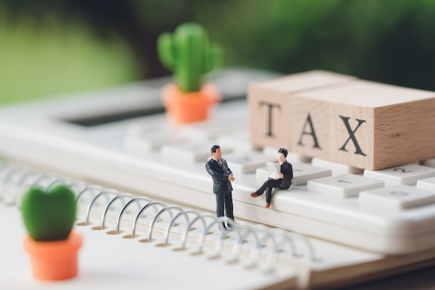 Pessoas em miniatura sentado consultoria consultoria para pagar impostos negócios