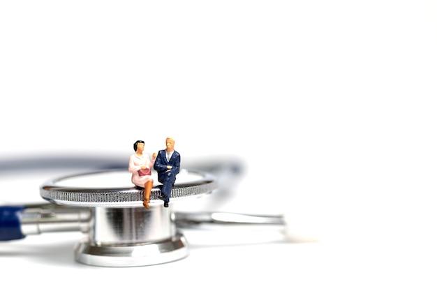 Pessoas em miniatura, sentado em um estetoscópio no fundo branco