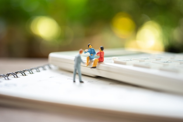 Pessoas em miniatura, sentado na calculadora branca usando como conceito de negócio de fundo