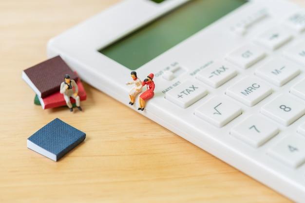 Pessoas em miniatura, sentado na calculadora branca usando como negócios de fundo