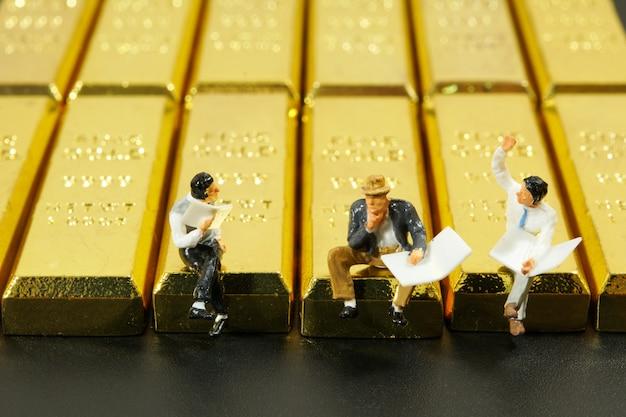 Pessoas em miniatura, sentado na pilha de barra de ouro sobre fundo preto