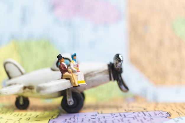 Pessoas em miniatura, sentado no avião com fundo de mapa do mundo