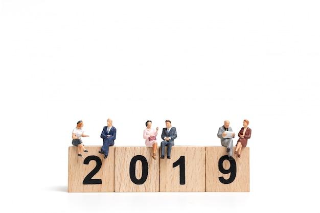 Pessoas em miniatura, sentado no bloco de madeira número 2019
