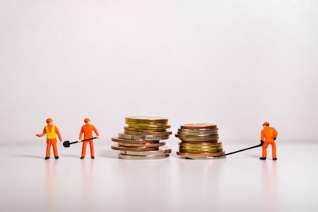 Pessoas em miniatura, técnico trabalhando em moedas de pilha