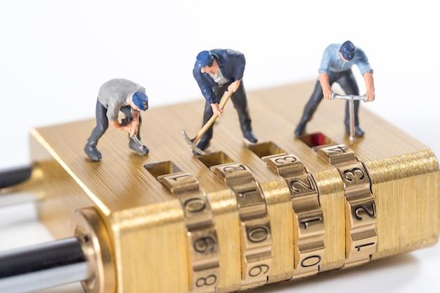 Pessoas em miniatura tentam desbloquear chave de bloqueio de segurança de metal