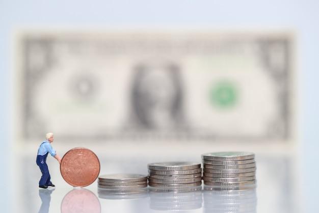 Pessoas em miniatura: trabalhador com moedas, conceito de negócio usando como pano de fundo