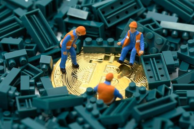 Pessoas em miniatura, trabalhador da construção civil escava uma moeda de ouro