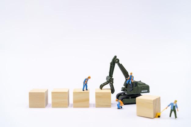 Pessoas em miniatura trabalhador da construção civil gerenciar produtos com bloco de madeira