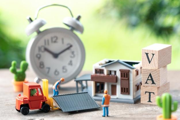 Pessoas em miniatura, trabalhador da construção civil um modelo de casa modelo é colocado com palavra de madeira