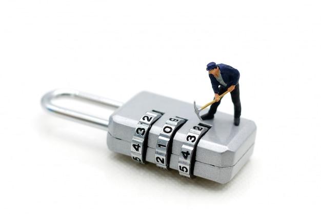 Pessoas em miniatura: trabalhador hacking na segurança de cadeado.