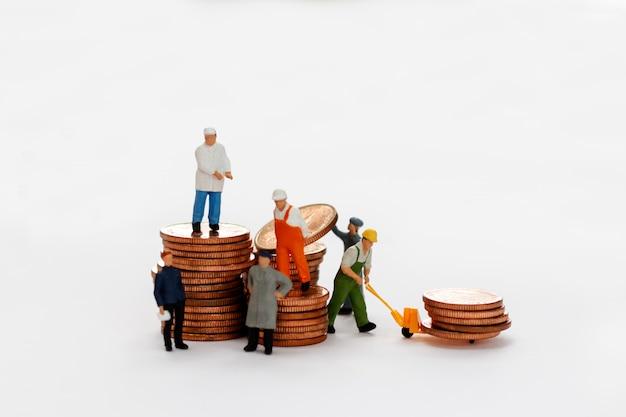 Pessoas em miniatura: trabalhadores movem pilha de moedas.