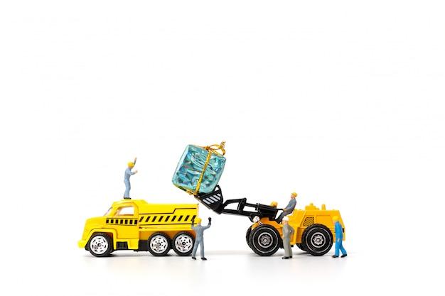 Pessoas em miniatura, trabalhando em uma caixa de presente