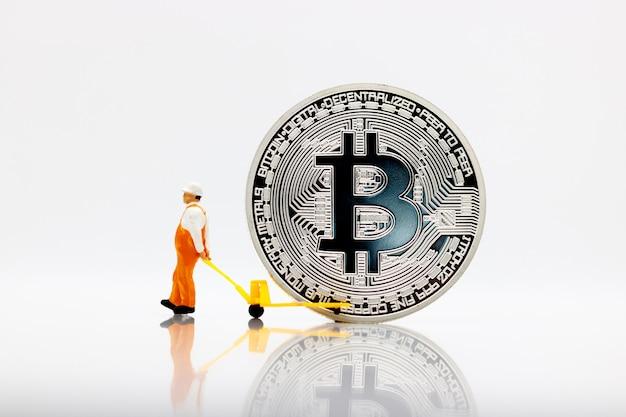 Pessoas em miniatura trabalhando transportando bitcoin dourado.