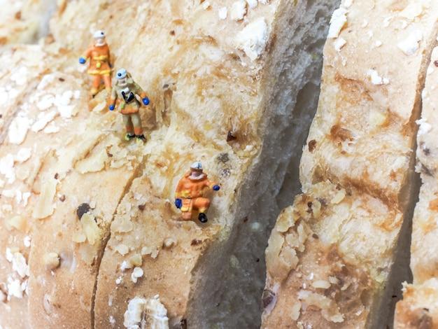 Pessoas em miniatura: três exploradores estão subindo uma montanha de quilos de pão.