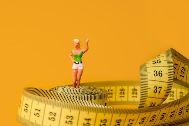 Pessoas em miniatura, uma mulher em um labirinto de fita métrica, o conceito de dieta e perda de peso