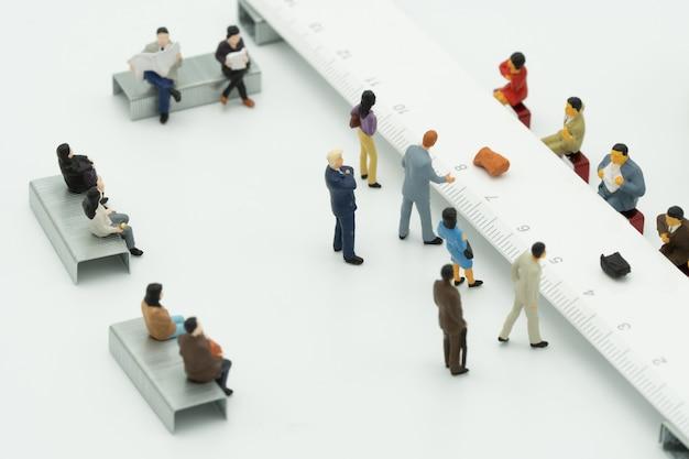 Pessoas em miniatura usam depósito em dinheiro. no balcão do banco ou instituição financeira.