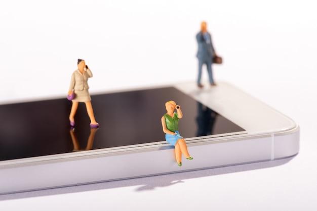 Pessoas em miniatura usando telefones móveis