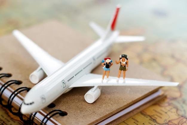Pessoas em miniatura: viajando com uma mochila viajando de avião.