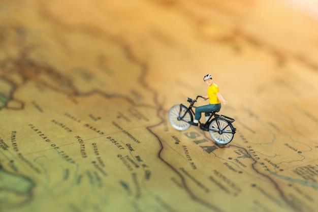 Pessoas em miniatura: viajando com uma mochila viajando de bicicleta.