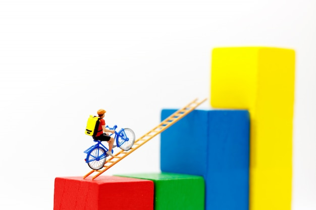 Pessoas em miniatura: viajante andando de bicicleta na escada de madeira com gráfico de crescimento, conceito do caminho para o objetivo e sucesso.