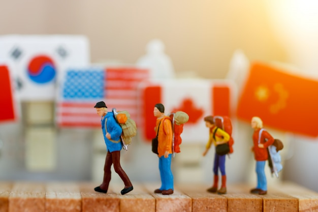 Pessoas em miniatura: viajante com mochila andando caixa de madeira.