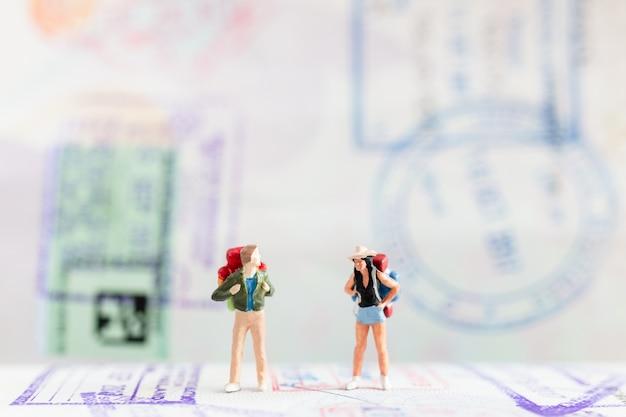 Pessoas em miniatura: viajante com mochila andando no passaporte