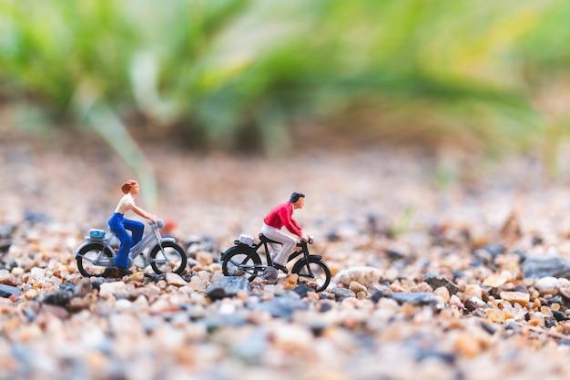 Pessoas em miniatura: viajantes andando de bicicleta na areia