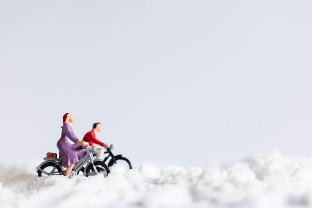 Pessoas em miniatura: viajantes andando de bicicleta na neve