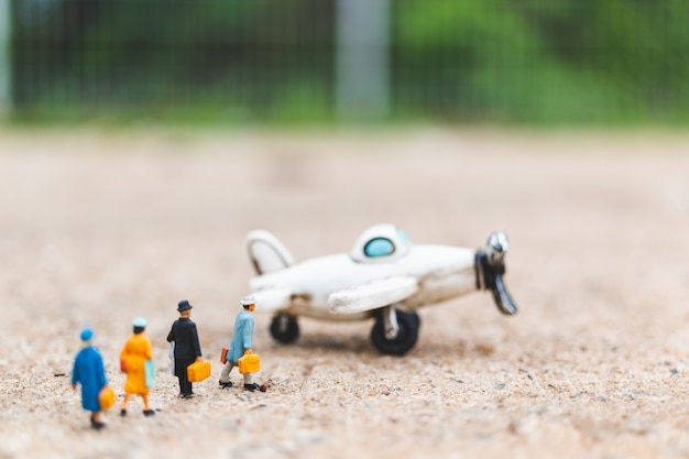 Pessoas em miniatura: viajantes segurando bagagem de mão entrar no avião