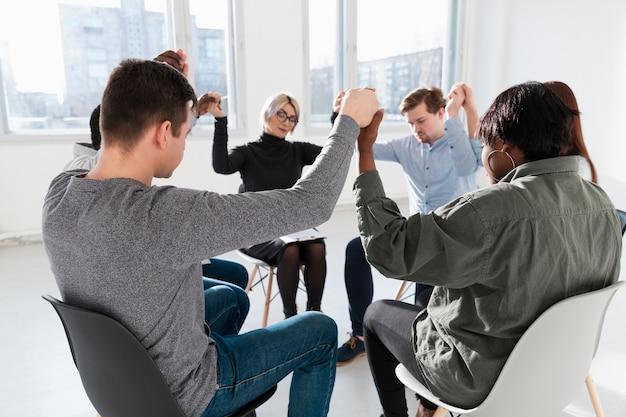 Pessoas em pé com os olhos fechados e levantando as mãos