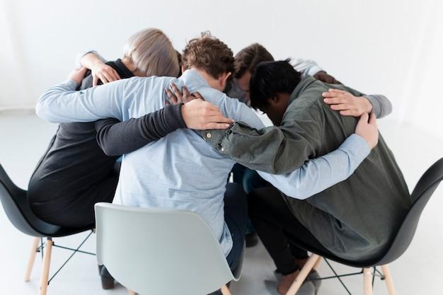 Pessoas em pé em cadeiras e abraçando