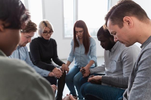 Pessoas em pé em um círculo com os olhos fechados e de mãos dadas