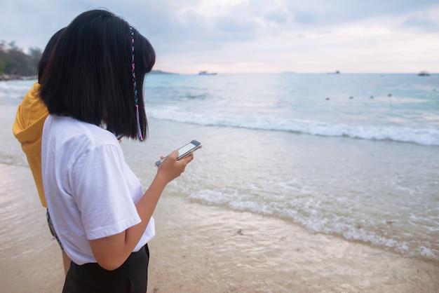 Pessoas em pé no telefone ao longo da costa.