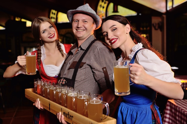 Pessoas em roupas da baviera com uma placa de cerveja e óculos contra um fundo de bar