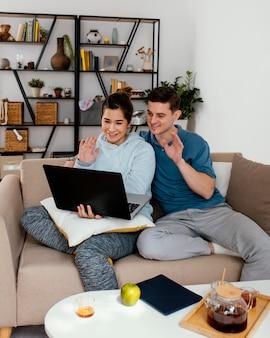 Pessoas em tiro médio acenando para um laptop