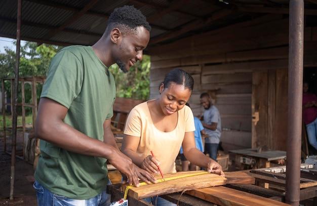 Pessoas em tiro médio medindo madeira