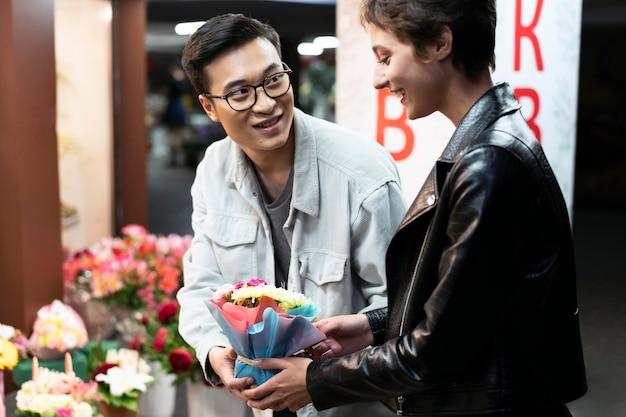 Pessoas em tiro médio segurando flores