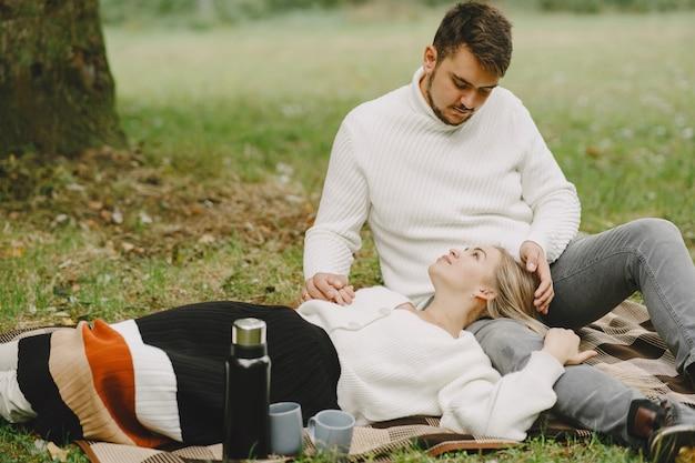 Pessoas em um parque. mulher com um casaco marrom. homem com um suéter branco. casal em um piquenique.