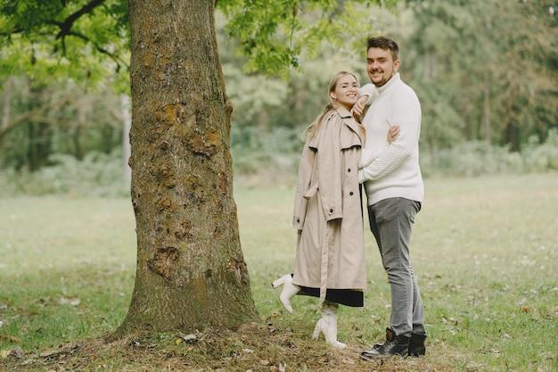 Pessoas em um parque. mulher com um casaco marrom. homem com um suéter branco.